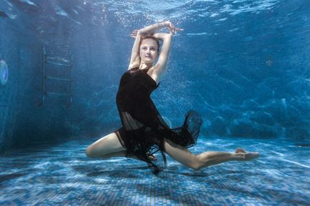 ドレスを着た女性がプールで水の下で踊って、彼女はスポーツの水中ダンスで従事しています。