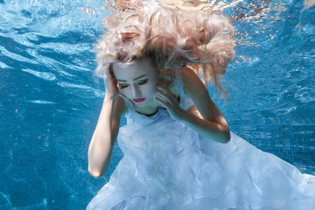 Blond woman in a white dress is under the water in the pool, her hair is roaring in the water. Stock Photo