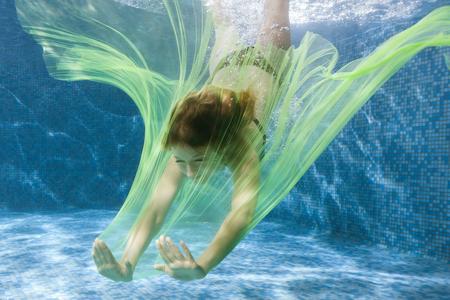 女性とプールで水の下で布のダイブします。