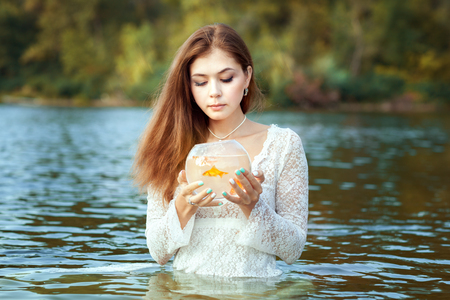 Woman makes a wish, in her hands a goldfish in an aquarium.