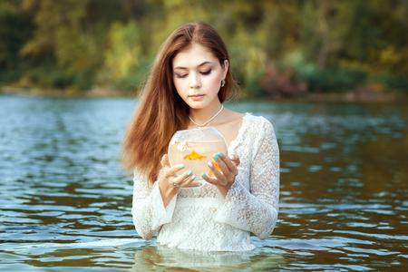 plea: Woman makes a wish, in her hands a goldfish in an aquarium.