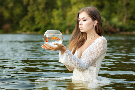 Woman stands in the water, in her hands an aquarium with goldfish, she makes her wishes come true.