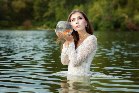 Woman listens to a goldfish, she dreams of desire.