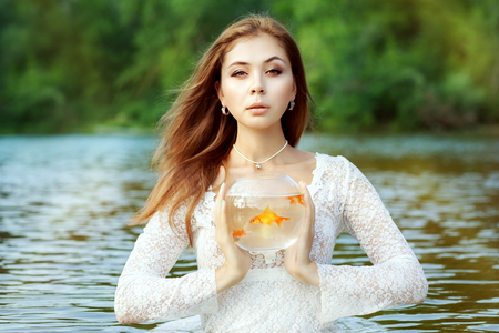 Woman is holding a goldfish in an aquarium, she wants to come up with a wish.