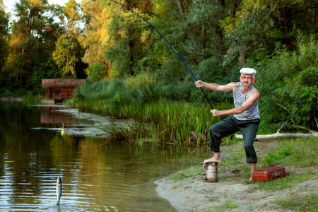 An old fisherman caught a fish in a lake, among the forest.