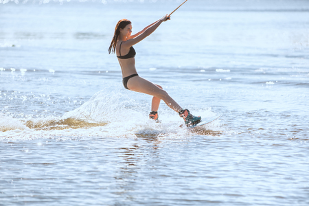 waterskiing: Woman in a swimsuit rides on wakeboarding, around splashes of water. Stock Photo