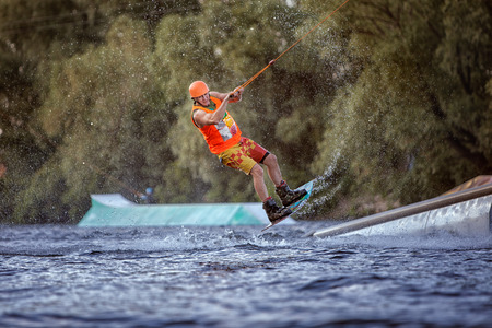 waterskiing: Man jumps on the water on a wakeboard, he is an extreme sportsman. Stock Photo