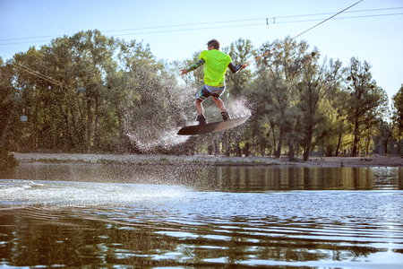 waterskiing: Man is engaged in extreme sports, he jumps on the board on the water.
