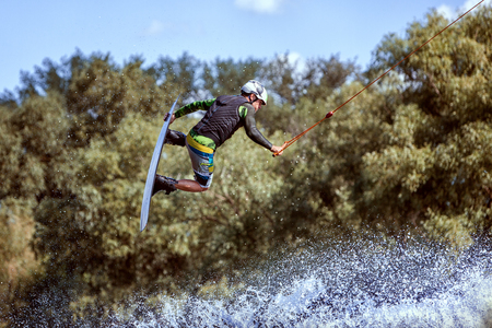 waterskiing: Wakeboarder sportsman jumping in a water park during training.