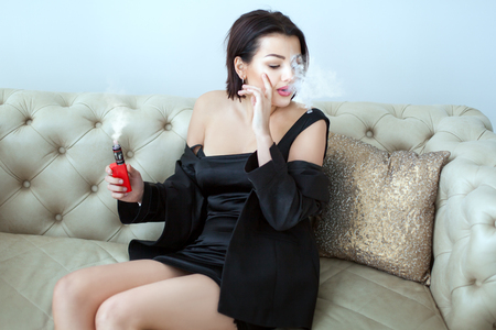 Young woman smokes an e-cigarette while sitting on the couch. She behaves defiantly.