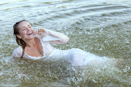 Woman swims in the water during a shower, she rejoices and rejoices.