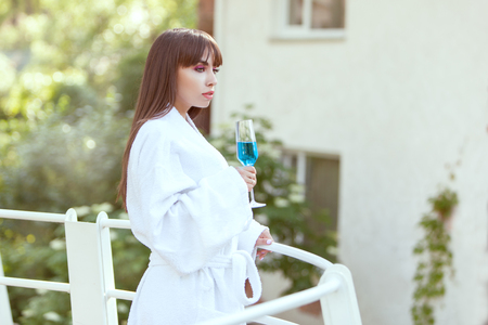 fruition: Woman is on the balcony of the hotel with a glass of wine in her hand, she is on vacation.