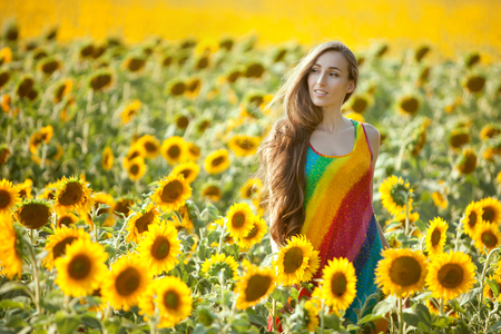 Young woman is standing in a field among sunflowers.
