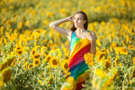 On the yellow field of sunflowers stands a young woman, a summer bright day. Stock Photo