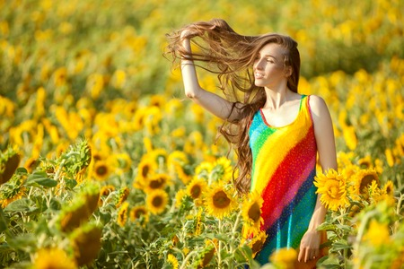 fruition: Woman with long hair is standing in the field among sunflowers.