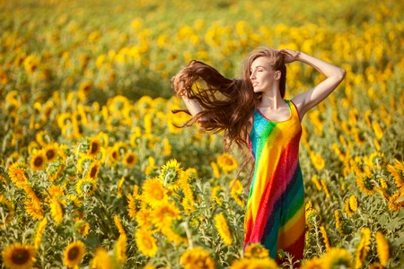 fruition: Womans hair is fluttering in the wind, she is standing in the field of sunflowers.