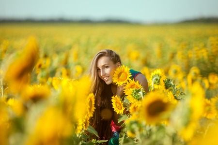 Young woman among yellow sunflowers in a field.