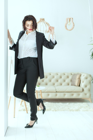 Young and charismatic woman dances near the wall, on it is a stylish business suit.