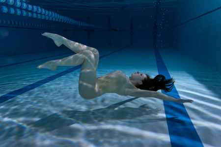 Swimmer in the pool under the water demonstrates the figures.