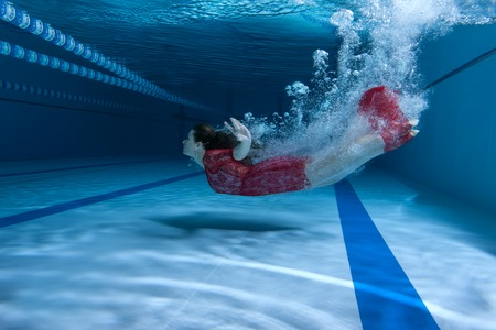 Swimmer in a dress dives underwater creating many bursts. Stock Photo