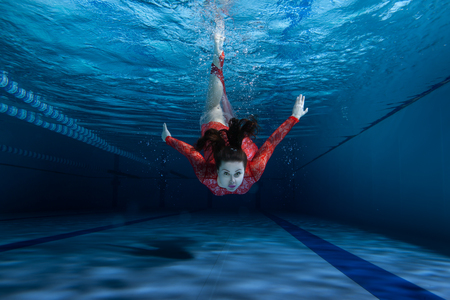 sinking: Swimmer dives into the pool, wearing a red dress.