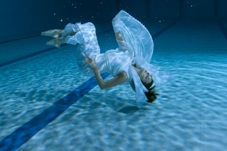여자는 수 중 쇼를 보여줍니다, 그녀는 수영장의 하단에 있습니다. 스톡 콘텐츠