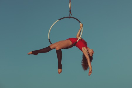 Woman is an aerial acrobat, she demonstrates the show on the hoop. Stock Photo
