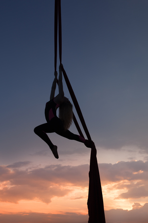 womans silhouette in air against the background of the evening zakazt, she carries out acrobatic tricks on cloths. Stock Photo