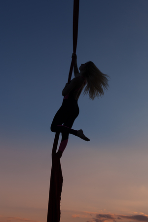 Acrobatic stunts on the canvas against the evening sunset sky.