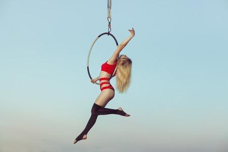 Weibliche Akrobat während der Präsentation der Show in der Luft auf dem Reifen. Standard-Bild - 83769207
