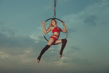 Acrobatics on a hoop against the background of the sky. The woman shows tricks at height in air. Stock Photo