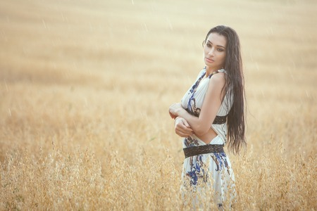 Woman enjoys the rain in a wheat field. Rain drops fall on it and it gets wet.