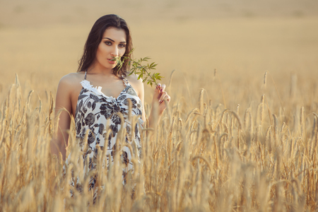 Woman in a village on a wheat field, evening sunset time.