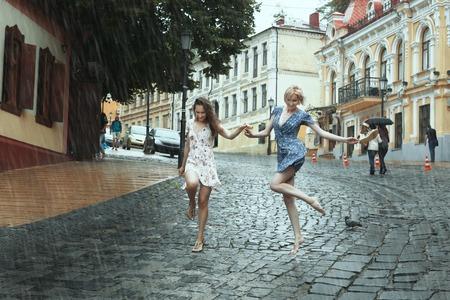 Women girlfriends stroll in the rain, they cheerfully jump.