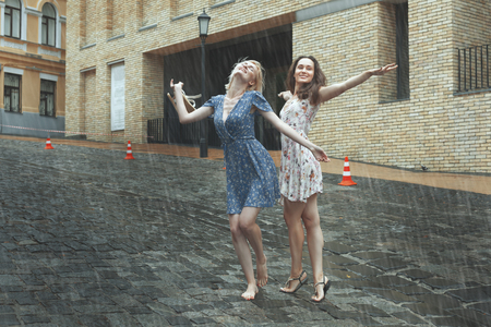 Women are happy with the rain, they are happy and dancing in the rain. Stok Fotoğraf - 84778087