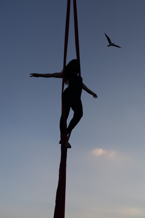 Woman acrobat on a hammock high in the sky. Stock Photo