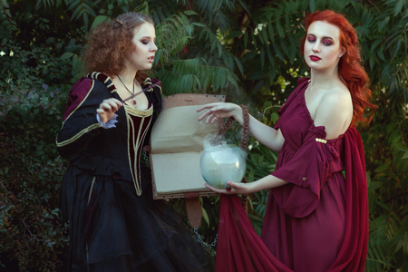 Women read a magic book and utter spells, they are witches.