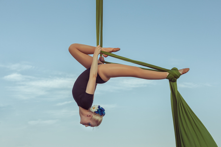 Woman air gymnast performs a trick on a hammock high in the sky. Stock Photo