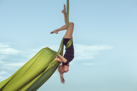 Woman the equilibrist flies in the sky on a hammock.
