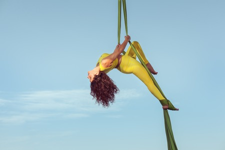 Woman the equilibrist gives a performance in the sky on a hammock.