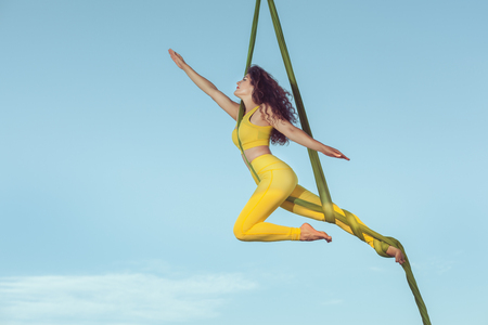 Female athlete by aerial acrobatics, she makes a performance high in the sky. Stock Photo