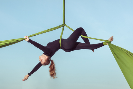 Woman the air equilibrist carries out tricks on a hammock.