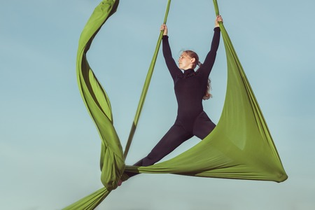 Sporting tricks on a hammock, woman aerial acrobat.