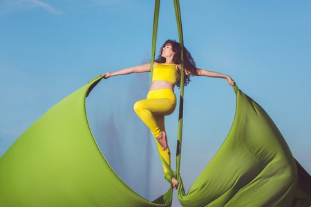 Athlete aerial acrobatics on a hammock, she stands high in the sky. Stock Photo