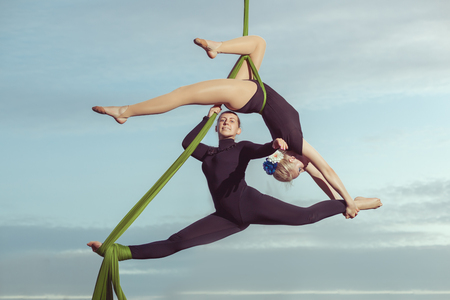Two women aerial gymnasts perform high in the sky on hammocks.