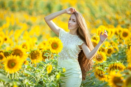 Woman with long hair in a field with sunflowers.