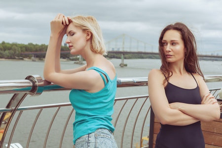 The women are standing on the bridge, they quarreled. Stock Photo