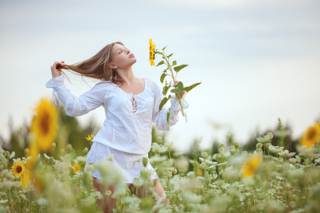 Woman in the field in the morning, amidst yellow flowers.