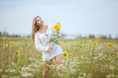 Lovely woman in the morning in the field, she is holding a yellow flower.