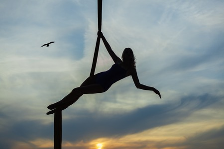 Woman aerial acrobat on the background of the setting sun, she does the tricks.